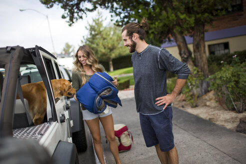 Young couple and dog preparing to load jeep for road trip - ISF12261