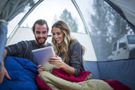 Young couple reading digital tablet in tent, Lake Tahoe, Nevada, USA - ISF12276