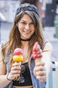 Young woman holding ice cream cones on street - ISF12312
