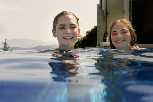 Surface level portrait of teenage girls in outdoor swimming pool - ISF12342