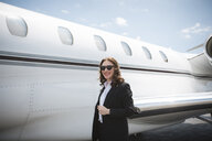 Portrait of female businesswoman and private jet at airport - ISF12399