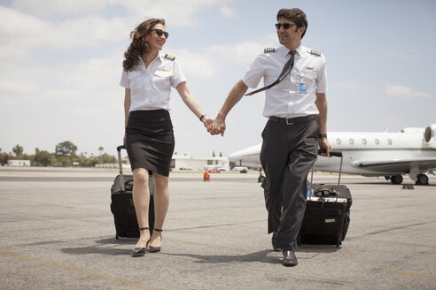 Male and female  private jet pilots holding hands at airport - ISF12414