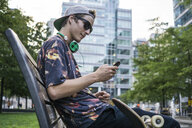 Young man using smartphone on park bench, Le Plateau, Montreal, Quebec, Canada - ISF12447