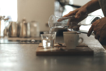 Man's hand pouring water into a glass in a coffee bar - OCAF00325