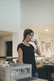 waitress in a coffee bar having a break drinking cup of coffee - OCAF00328