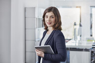 Portrait of smiling young businesswoman with tablet in office - RORF01261