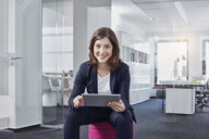 Portrait of smiling young businesswoman using tablet in office - RORF01264