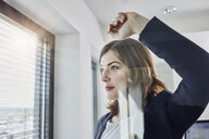 Confident young businesswoman looking out of window in office - RORF01267