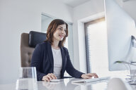 Smiling young businesswoman working at desk in office - RORF01270