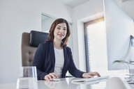 Portrait of smiling young businesswoman at desk in office - RORF01273