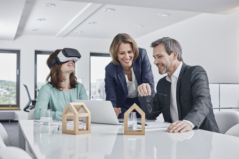 Business people having a meeting in office with VR glasses, laptop and architectural models - RORF01279