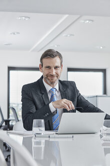 Portrait of confident businessman with laptop at desk in office - RORF01282