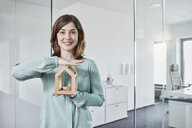 Portrait of smiling young businesswoman holding architectural model in office - RORF01285