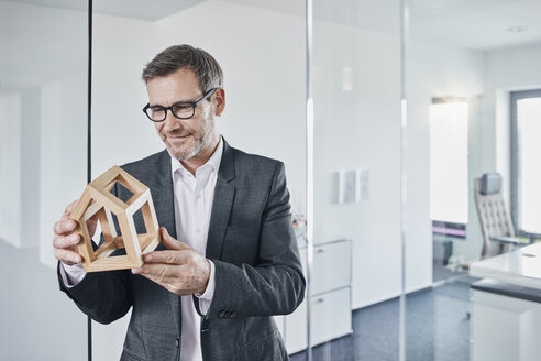 Smiling businessman looking at architectural model in office - RORF01291
