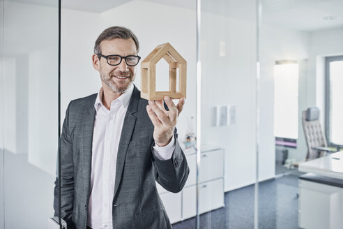 Smiling businessman looking at architectural model in office - RORF01294