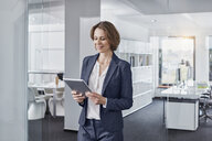 Businesswoman using tablet in office - RORF01306