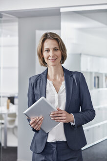 Portrait of smiling businesswoman holding tablet in office - RORF01309