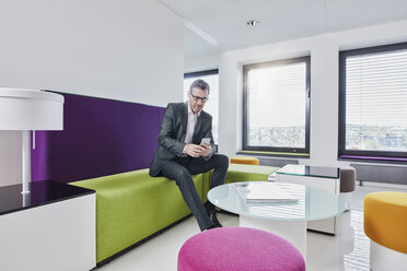 Businessman using smartphone in office lounge - RORF01324