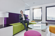 Happy businessman with smartphone in office lounge - RORF01327