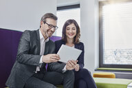 Smiling businessman and businesswoman using tablet in office lounge together - RORF01330