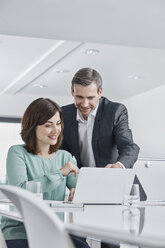 Businessman and businesswoman having a meeting in office with laptop - RORF01336
