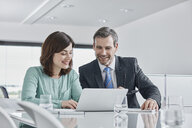 Businessman and businesswoman having a meeting in office with laptop - RORF01339
