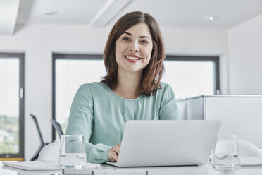 Portrait of smiling young businesswoman using laptop at desk in office - RORF01342