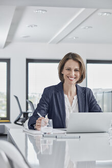 Portrait of smiling businesswoman using laptop at desk in office - RORF01345
