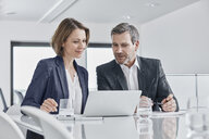 Businessman and businesswoman having a meeting in office with laptop - RORF01351