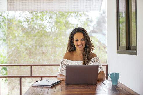 Woman using laptop at home - MOMF00449