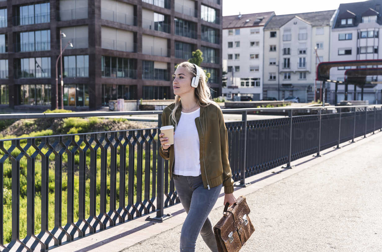 Young woman walking on bridge, drinking coffee, listening music with headphones - UUF14157 - Uwe Umstätter/Westend61