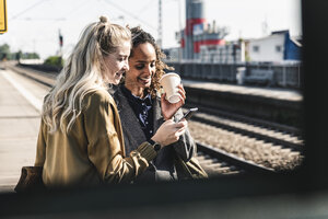 Friends waiting at train station looking at smartphone - UUF14163