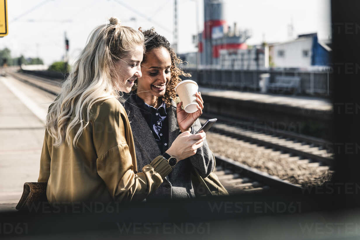 Friends waiting at train station looking at smartphone - UUF14163 - Uwe Umstätter/Westend61