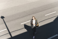 Young woman walking on empty road, talking into her smartphone - UUF14172