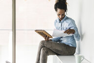 Young businesswoman sitting on shelf, using digital tablet, reading documents - UUF14187