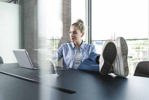 Young businesswoman sitting at desk with feet up, using laptop - UUF14223