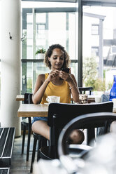 Young woman sitting in cafe, drinking coffee, reading text messages - UUF14247