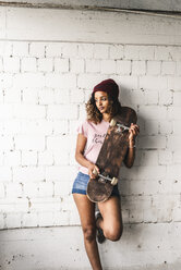 Portrait of a young woman with skateboard, leaning against wall - UUF14253