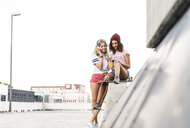 Best friends with skateboard, having fun together, listening music - UUF14256