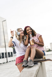 Best friends with skateboard, having fun together, listening music - UUF14259