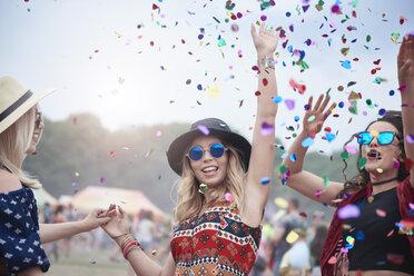 Friends dancing among confetti at the music festival - ABIF00602
