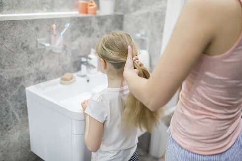 Mother combing daughter's hair in bathroom - AWF00074