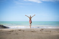 Thailand, Khao Lak, back view of happy woman standing on the beach at seaside - CHPF00480