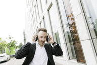 Young businessman wearing headphones in the city - KMKF00384