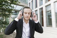 Young businessman with closed eyes wearing headphones outdoors - KMKF00387