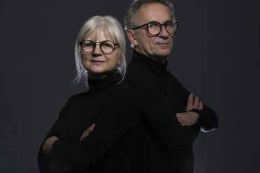 Portrait of senior couple wearing glasses in front of dark background - AWF00098