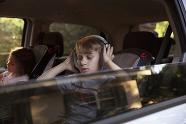 Boy with younger sister listening to headphones in car back seat - ISF12689