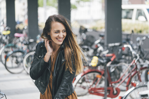 Portrait of happy young woman at bicycle parking station in the city - KNSF03984
