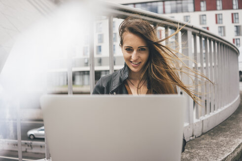 Portrait of smiling young woman with windswept hair using laptop on motorway bridge - KNSF03999