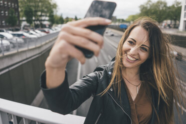 Smiling young woman taking a selfie on motorway bridge - KNSF04002